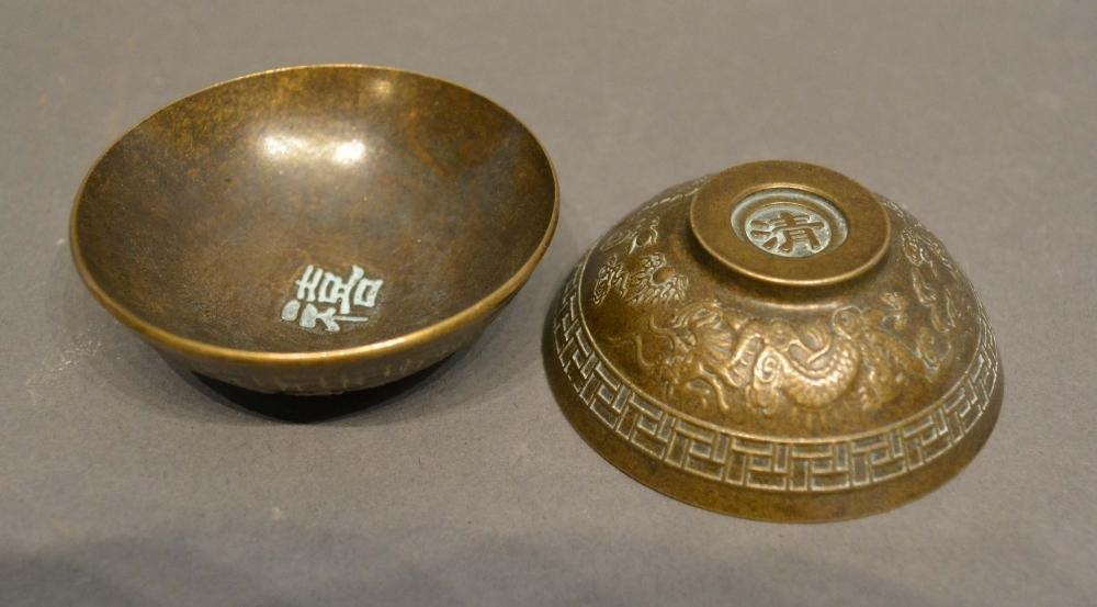 Lot 280 - A Pair of Chinese Patinated Bronze Small Bowls decorated in relief with serpents amongst foliage,