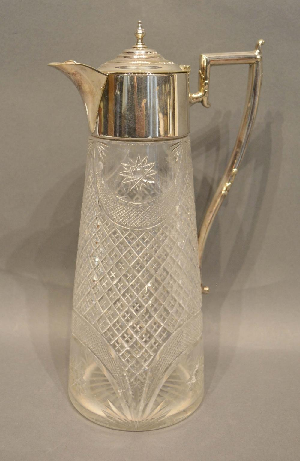 Lot 208 - An Edwardian Silver Plated and Cut Glass Claret Jug with shaped handle, 28cm tall