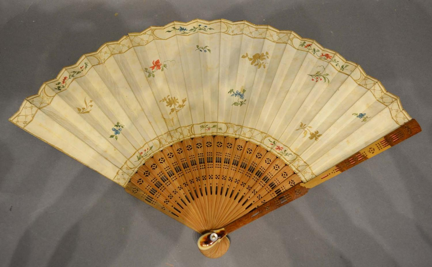 Lot 325 - A 19th Century fan, hand painted with reserves within gilded decoration with finely pierced sticks