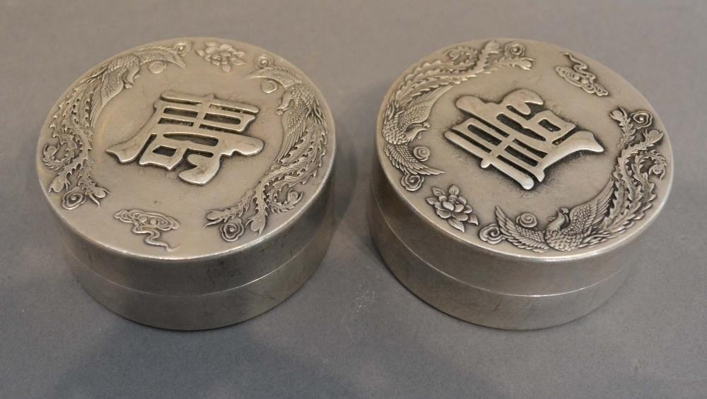 Lot 279 - A Pair of Chinese White Metal Cylindrical Covered Boxes, the covers decorated in relief with script,