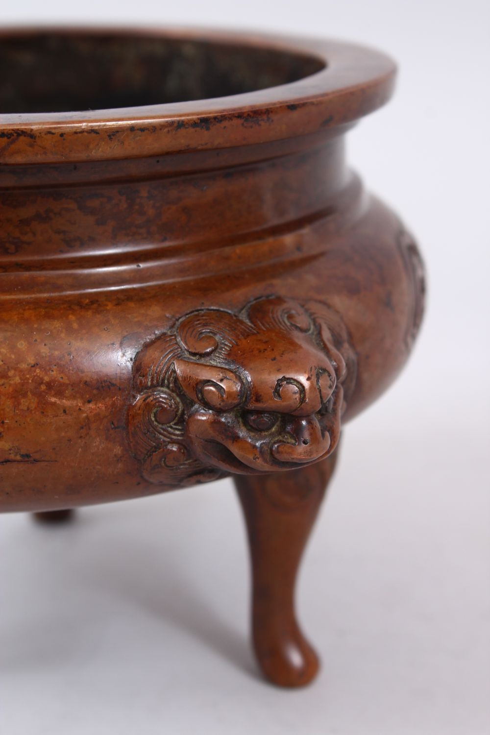 Lot 39 - A 19TH / 20TH CENTURY CHINESE BRONZE TRIPOD CENSER, eith moulded lion dog head handles, panels of