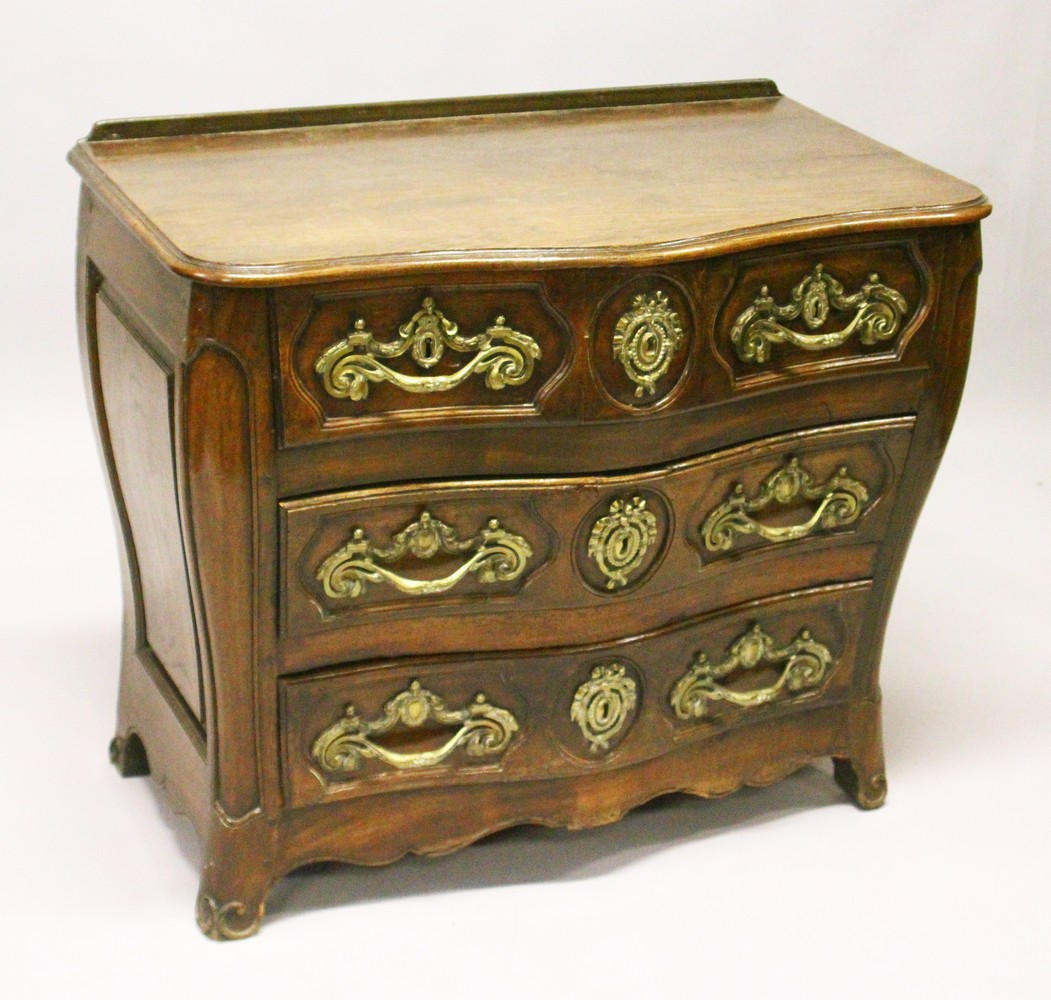 Lot 1012 - A LOUIS XV STYLE FRENCH OAK SERPENTINE FRONT COMMODE, comprising two short and two long drawers, all