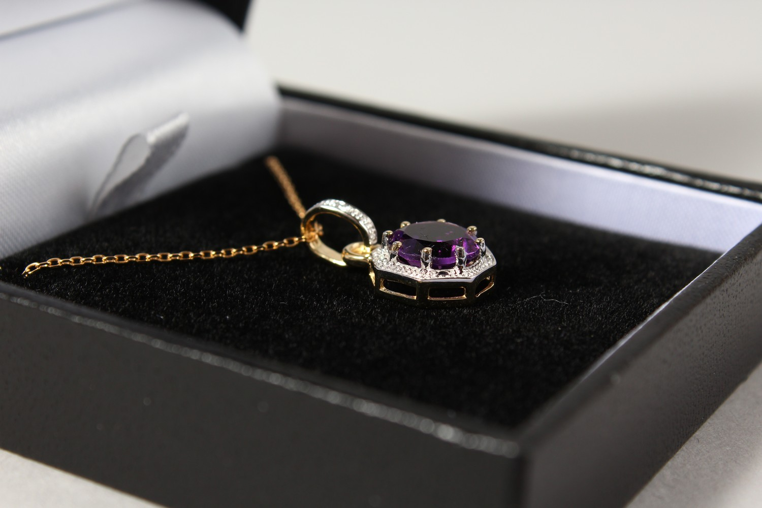 Lot 1785 - A 9CT GOLD, AMETHYST AND DIAMOND PENDANT AND CHAIN.