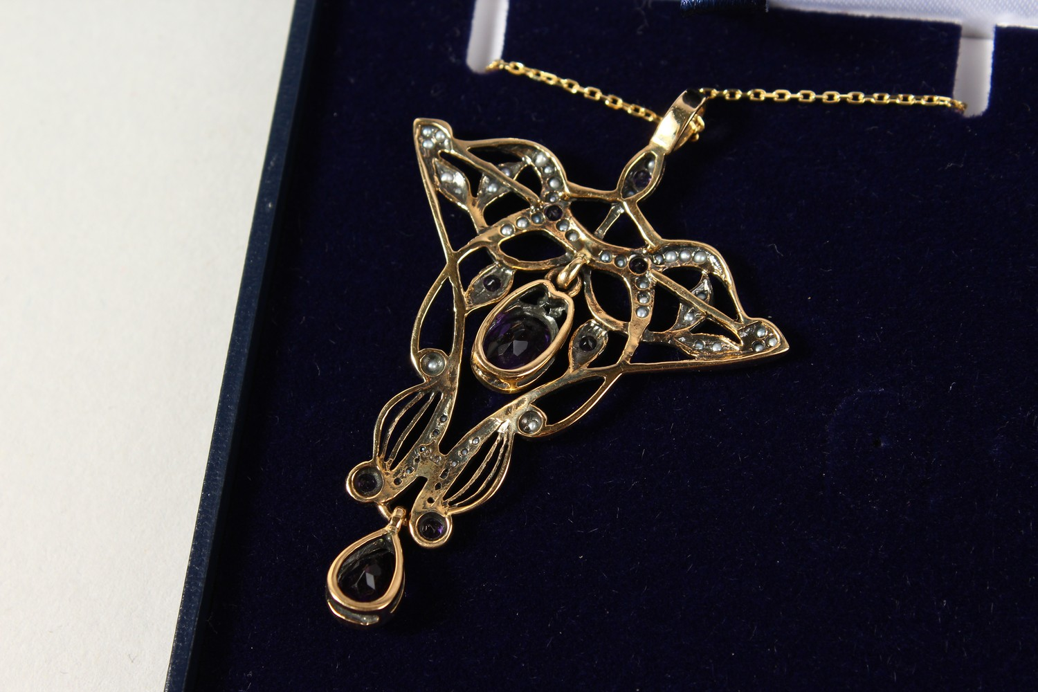 Lot 1760 - A 9CT GOLD, AMETHYST AND SEED PEARL ART NOUVEAU STYLE PENDANT AND CHAIN.