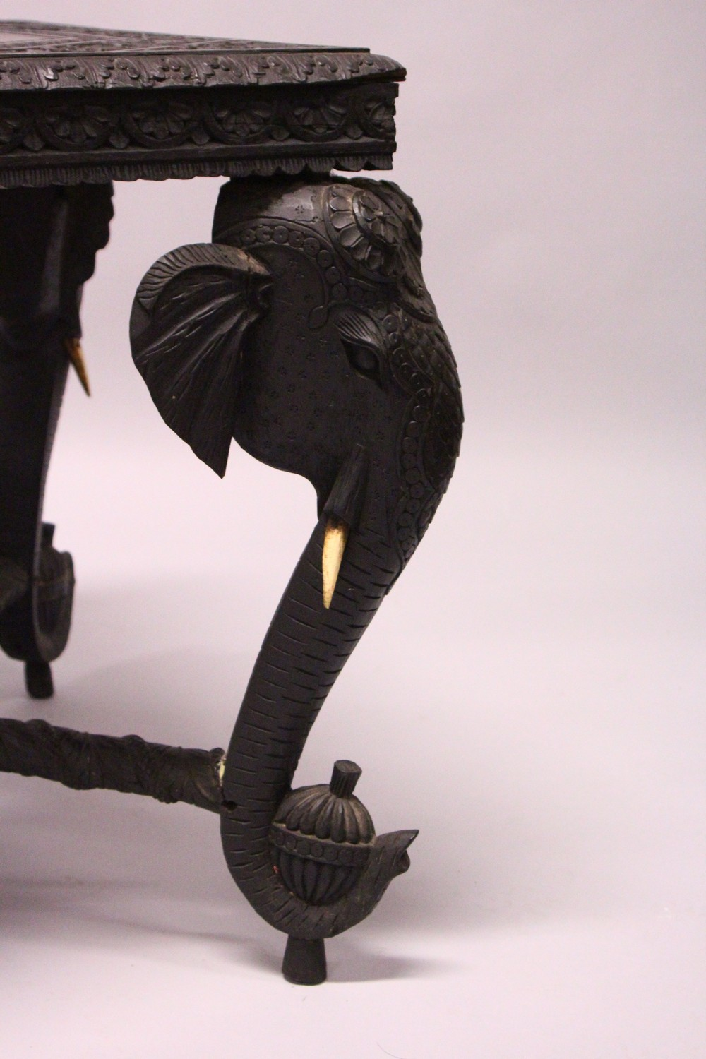 Lot 1017 - AN EARLY 20TH CENTURY CEYLONESE CARVED EBONY LOW TABLE, with an elephant head leg to each corner.