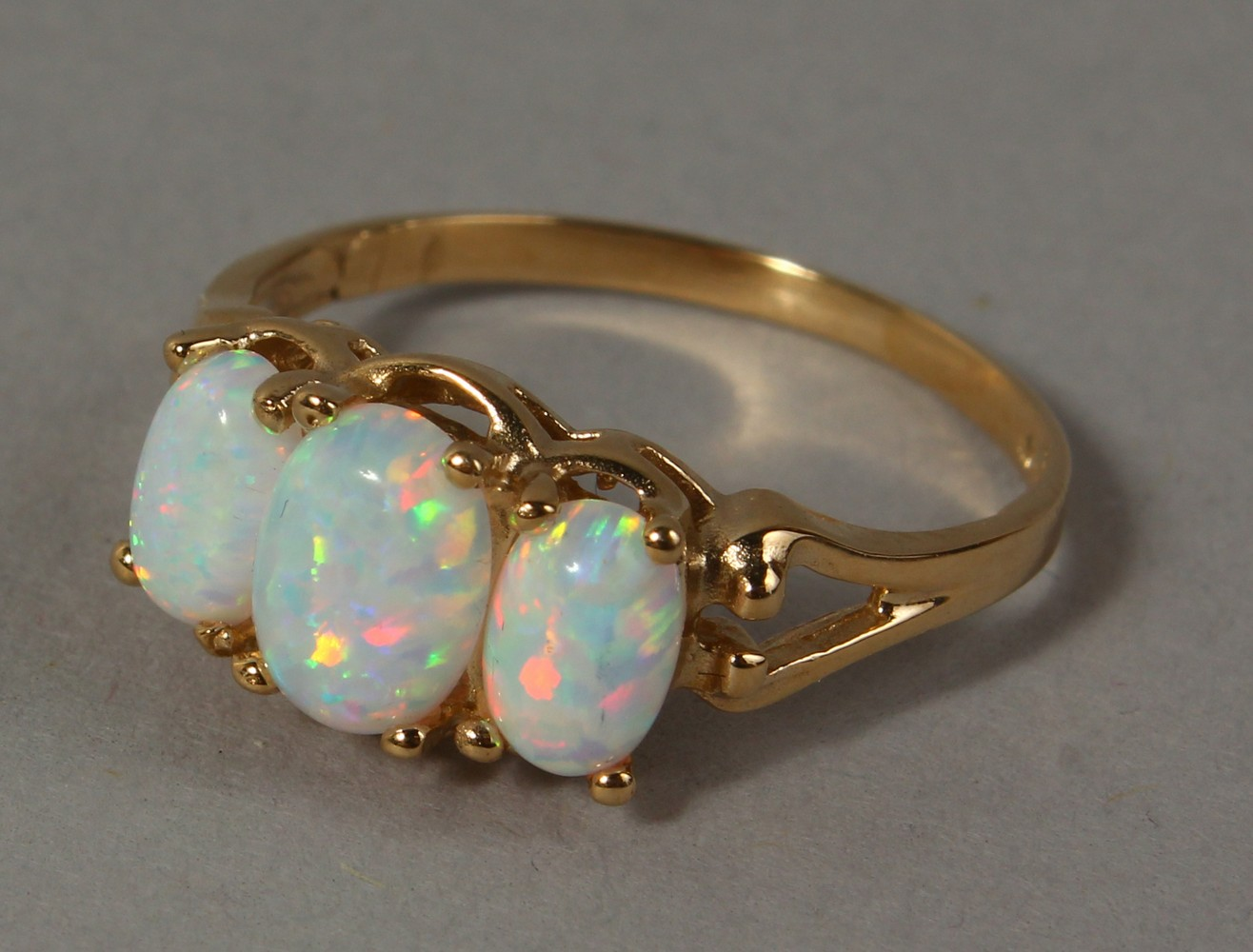 Lot 1765 - A 9CT GOLD THREE STONE OPAL RING.