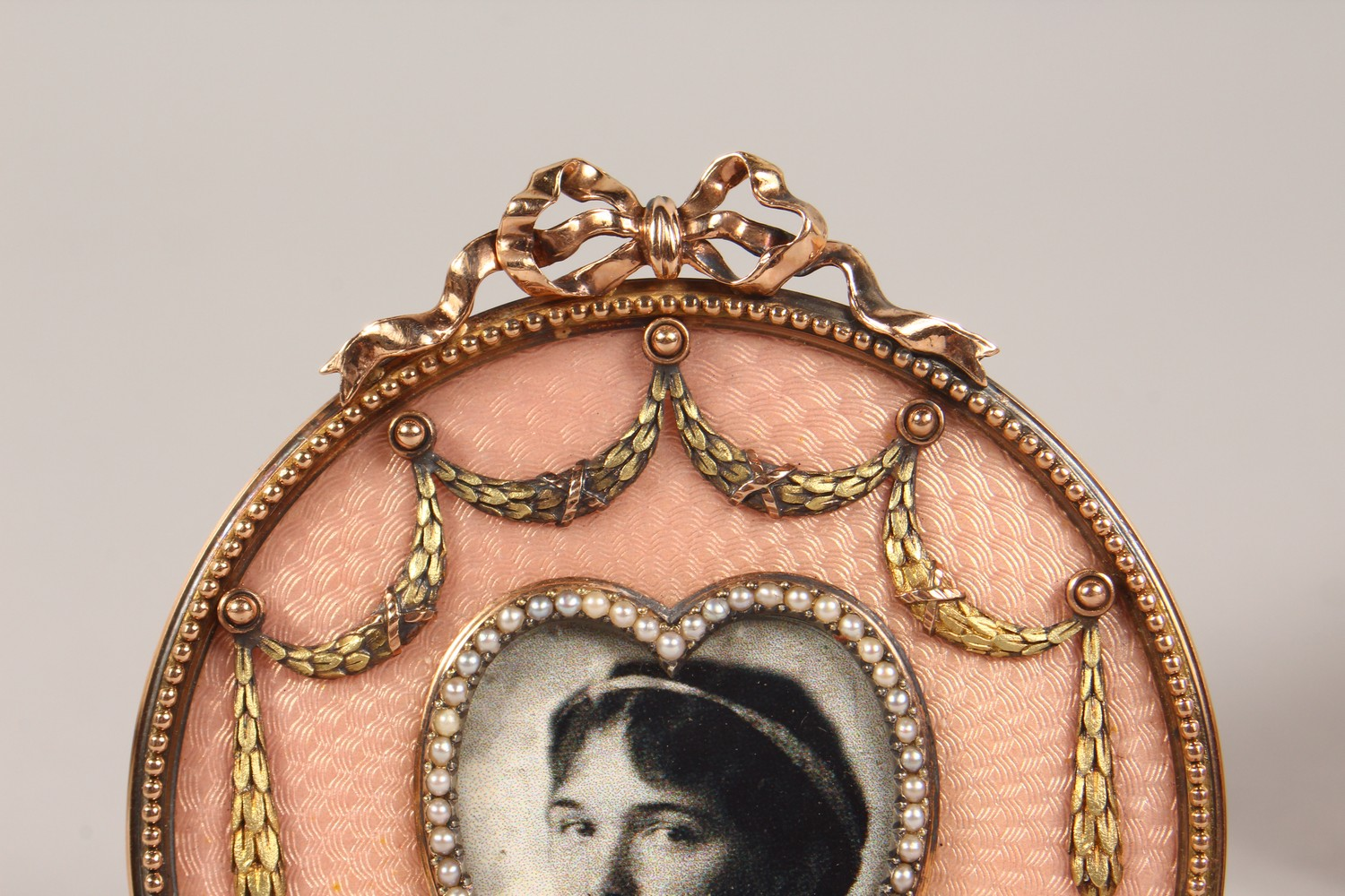 Lot 1673 - A VERY GOOD GOLD AND PINK GUILLOCHE ENAMEL SMALL CIRCULAR PHOTOGRAPH FRAME, with heart shape
