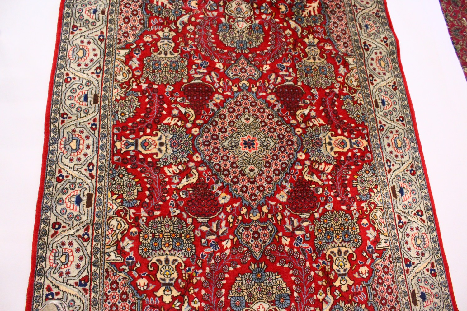 Lot 1032 - A PERSIAN ISFAHAN CARPET, red ground with central medallion, urns of flowers in a conforming