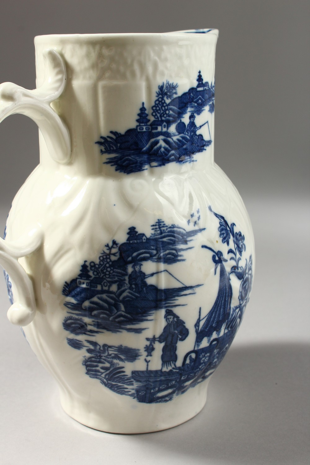 Lot 1071 - A CAUGHLEY BLUE AND WHITE JUG, of cabbage leaf shape with five scenes on it, Sx mark.