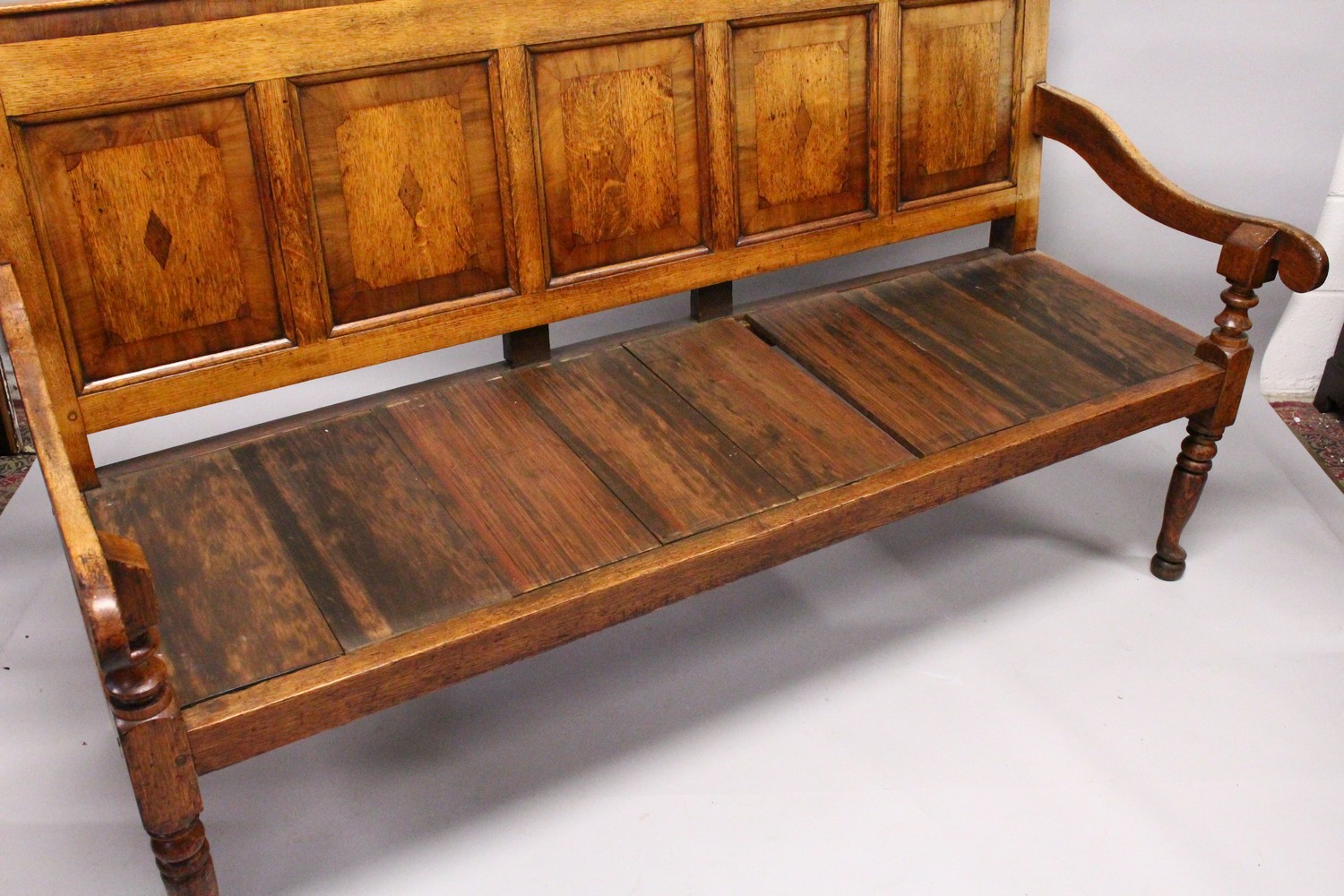 Lot 1029 - AN 18TH CENTURY OAK PANEL BACK SETTLE, with five mahogany banded panels, loose cushion, on turned