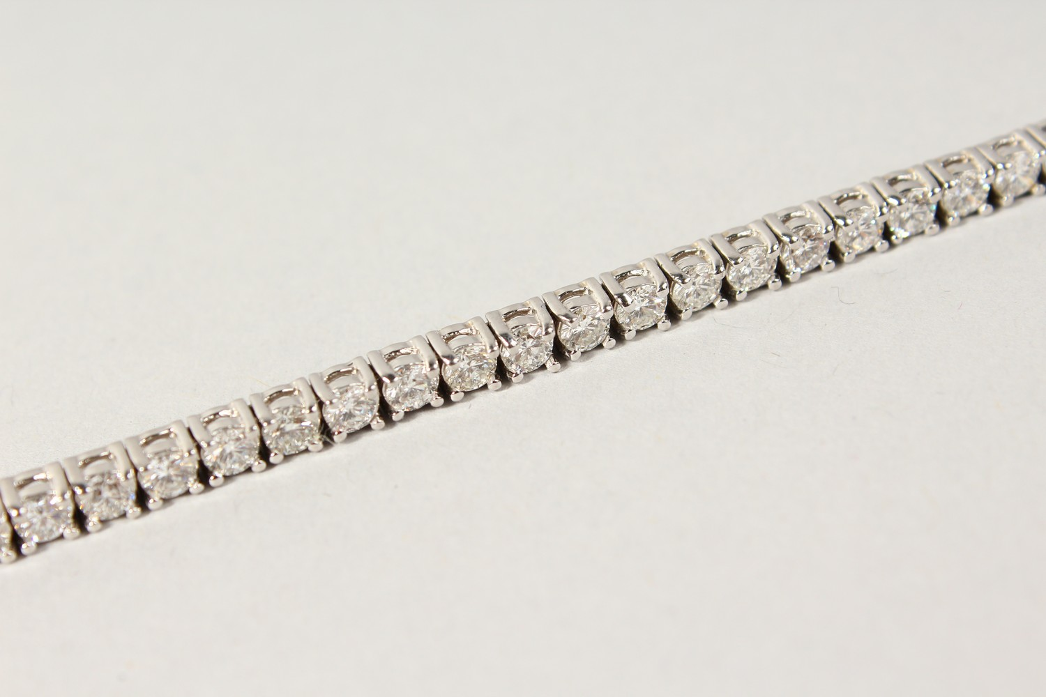 Lot 1741 - AN 18CT WHITE GOLD DIAMOND LINE BRACELET, with forty-nine diamonds, approx. 6CTS, G/H Colour, V1-