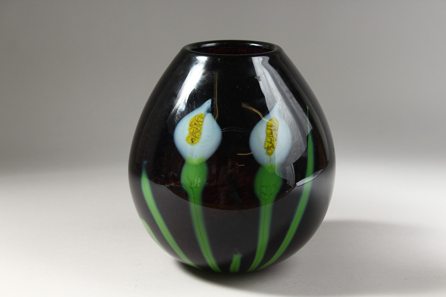 Lot 1055 - AN AMETHYST COLOUR STUDIO GLASS VASE, of bulbous shape, decorated with flowers, signed. 8.5ins