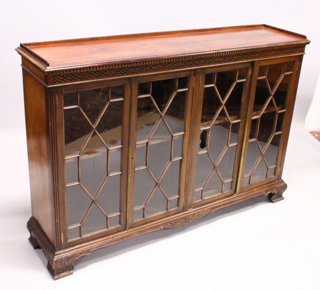 Lot 1030 - A GEORGE III DESIGN MAHOGANY LOW BOOKCASE, with dentil and blind fret cornice, four astragal