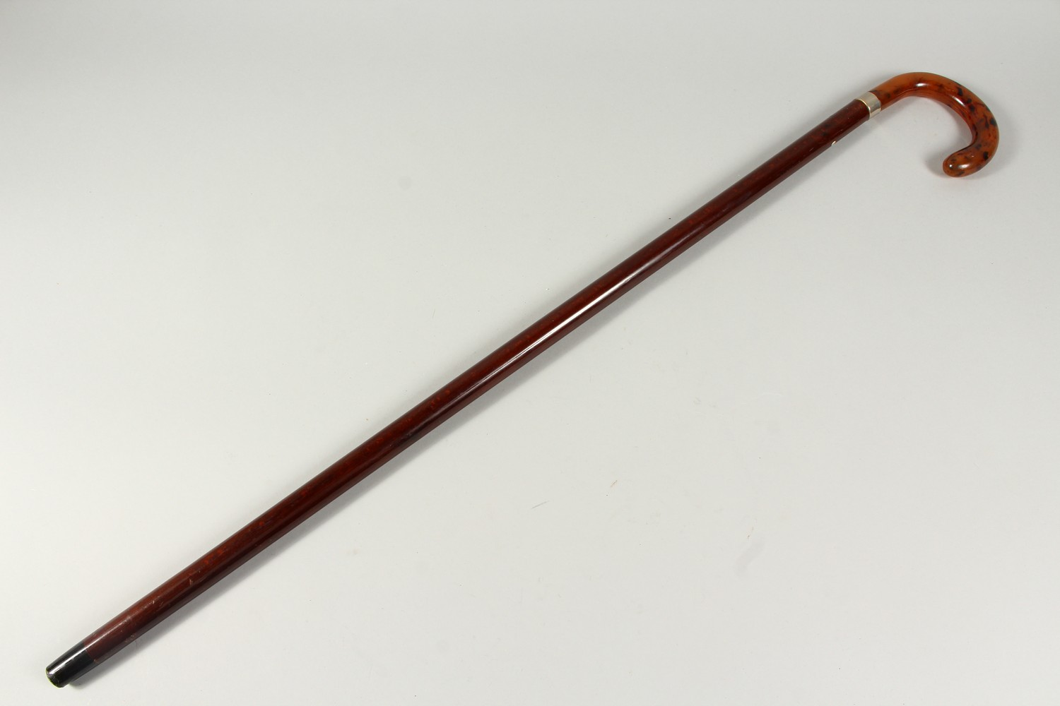Lot 1532 - A WALKING STICK with faux-tortoiseshell handle and silver band. Birmingham. 2ft 1in long.