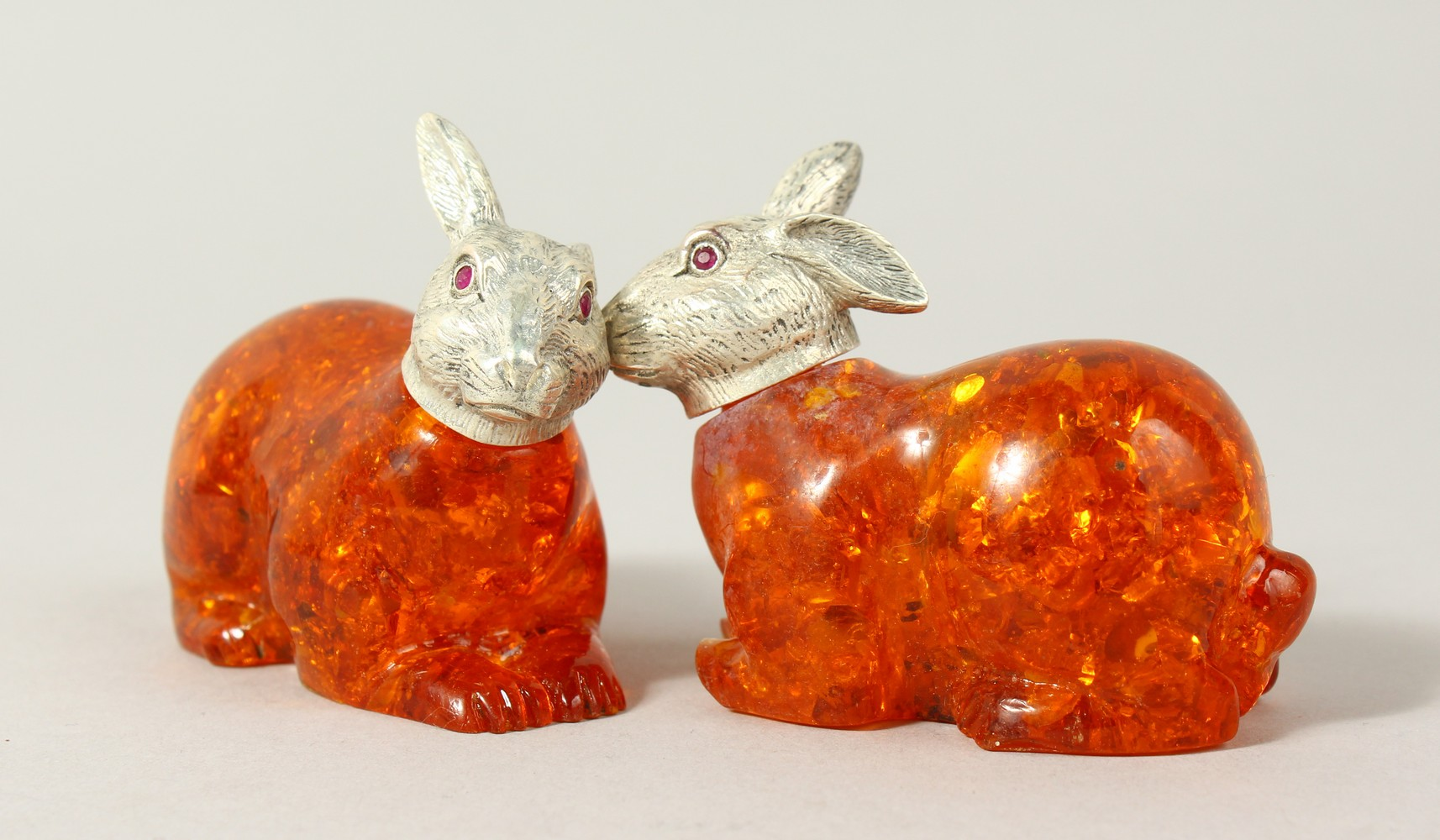 Lot 1626 - A PAIR OF AMBER RABBITS with plated heads. 2.5ins long.