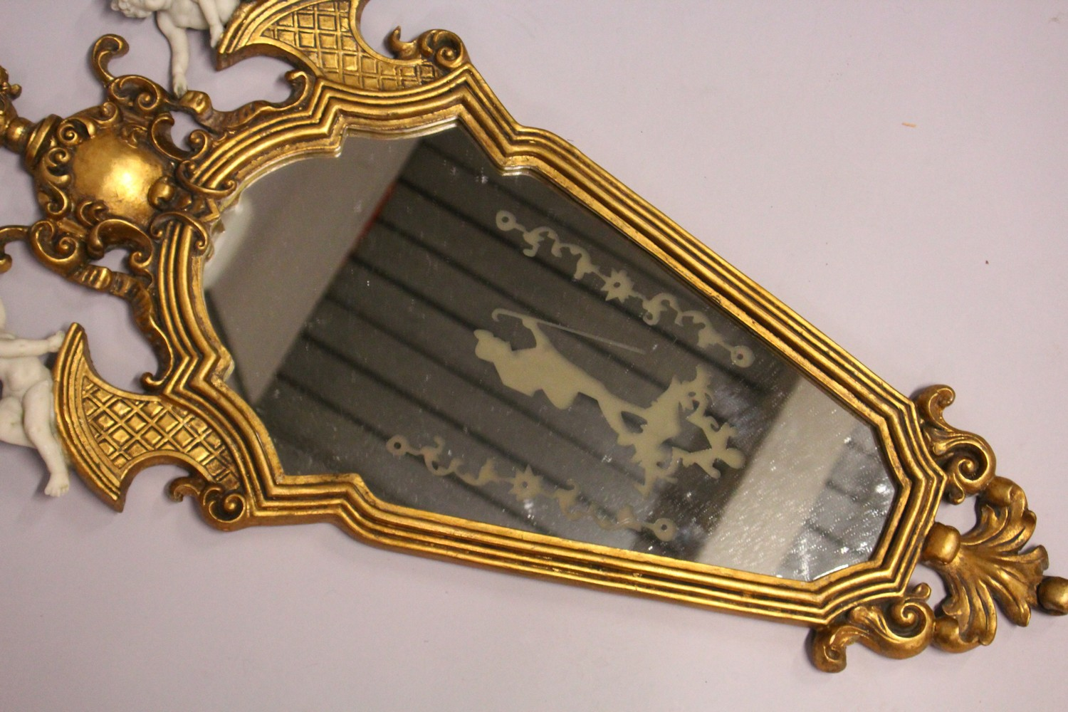 Lot 1015 - A FRENCH STYLE GILT FRAMED MIRROR, mounted with cherubs. 2ft 10ins high x 1ft 5ins wide.