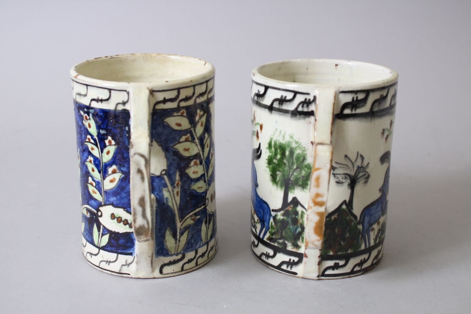 Lot 30 - TWO IZNIK STYLE POTTERY TANKARDS, 13cm high.