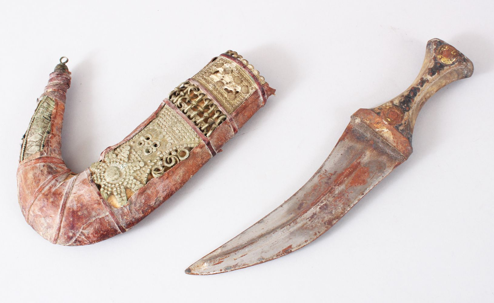 Lot 7 - A GOOD PERSIAN JAMBYA DAGGER, the sheath formed from white metal and leather, the handle formed from