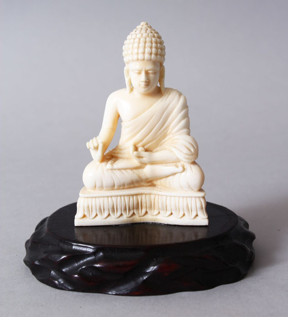 Lot 39 - A 19TH CENTURY INDIAN CARVED IVORY BUDDHA, in a seated meditation position, on its hard wood
