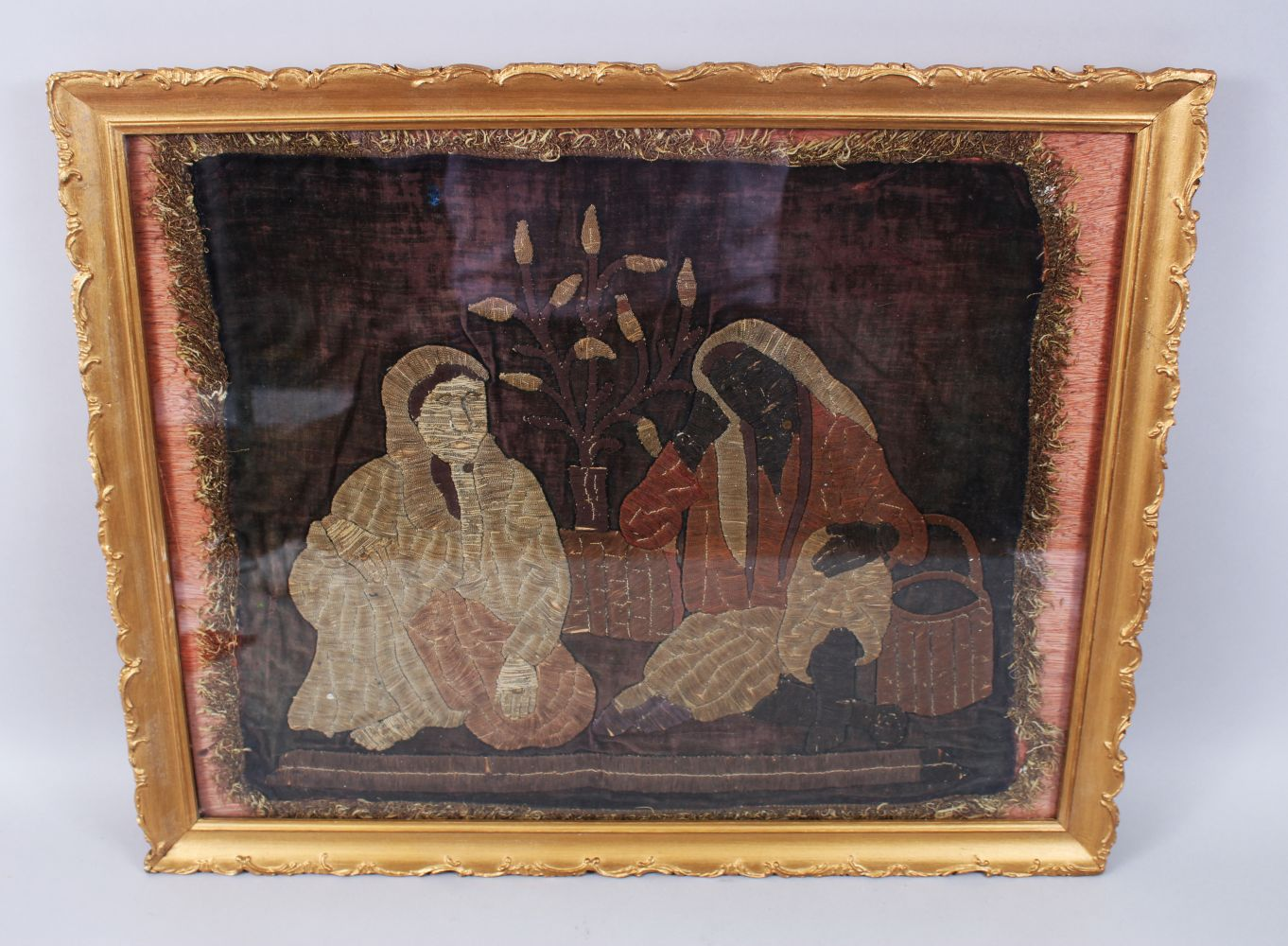 Lot 17 - A 19TH CENTURY OTTOMAN TURKISH EMBROIDED PICTURE OF TWO LADIES sitting with a vase of plants between