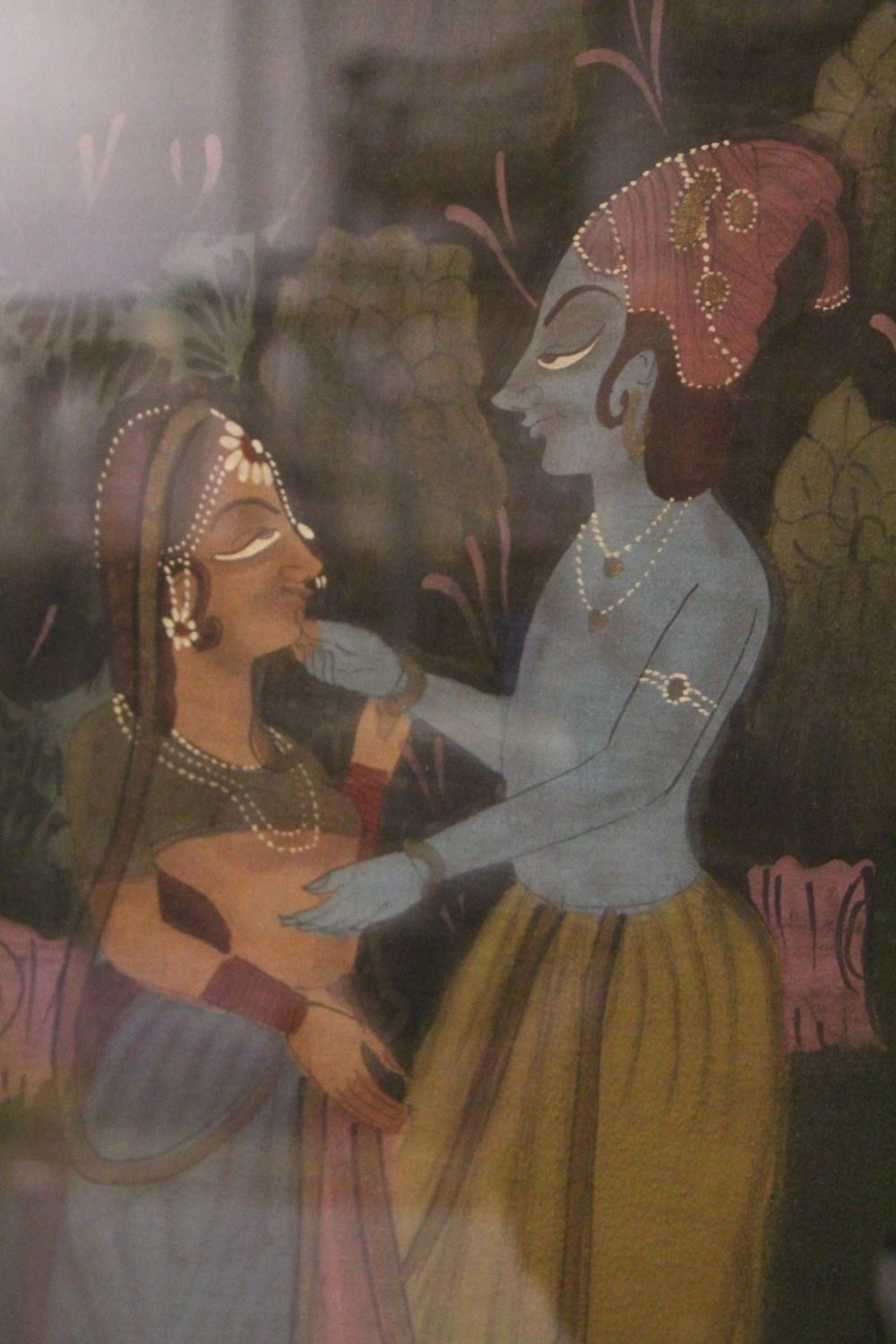Lot 44 - A 19TH-20TH CENTURY FRAMED INDIAN PAINTING ON TEXTILE depicting a blue skin god dancing with a