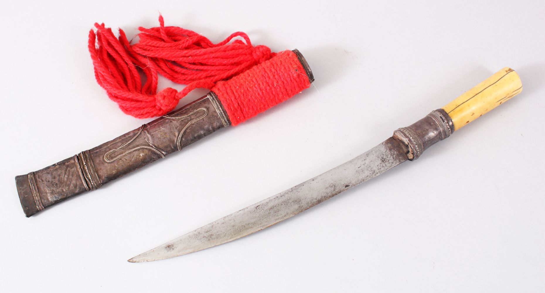 Lot 3 - A GOOD PERSIAN / INDIAN BONE HANDLE DAGGER, with a white metal sheath, with red tassels,32.5cm