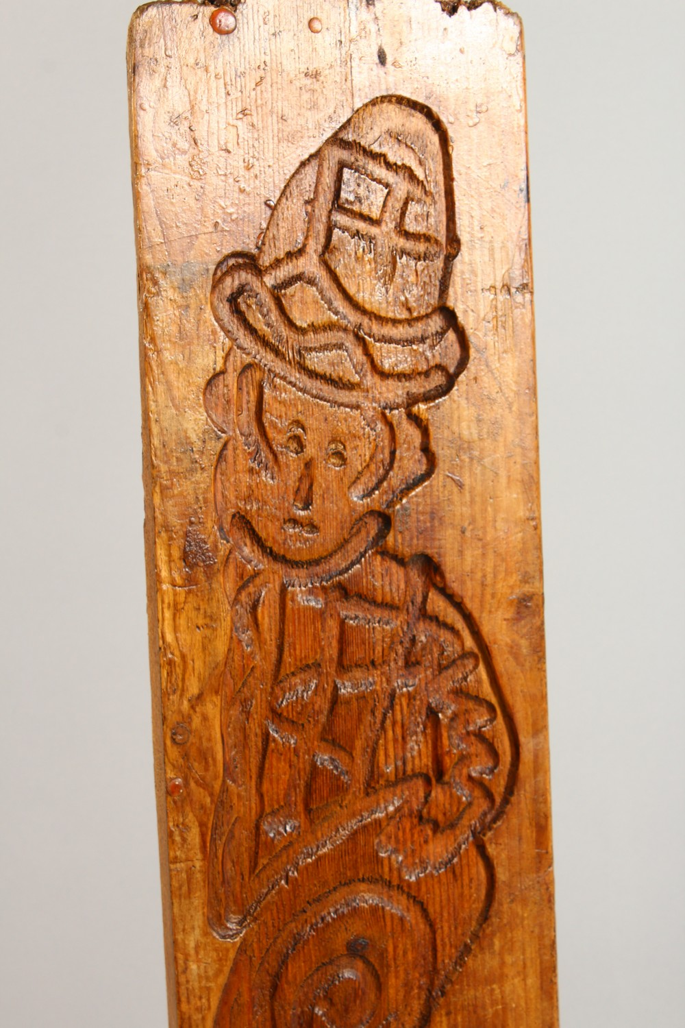 Lot 1554 - A 19TH CENTURY SINGLE SIDED PINE GINGERBREAD MOULD, carved with a figure of a man. 33ins x 8ins.