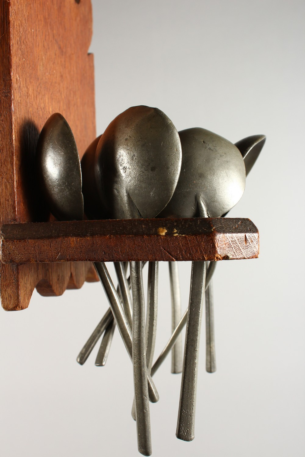 Lot 1494 - AN OAK SPOON RACK, with ten pewter spoons. 10.5ins high.
