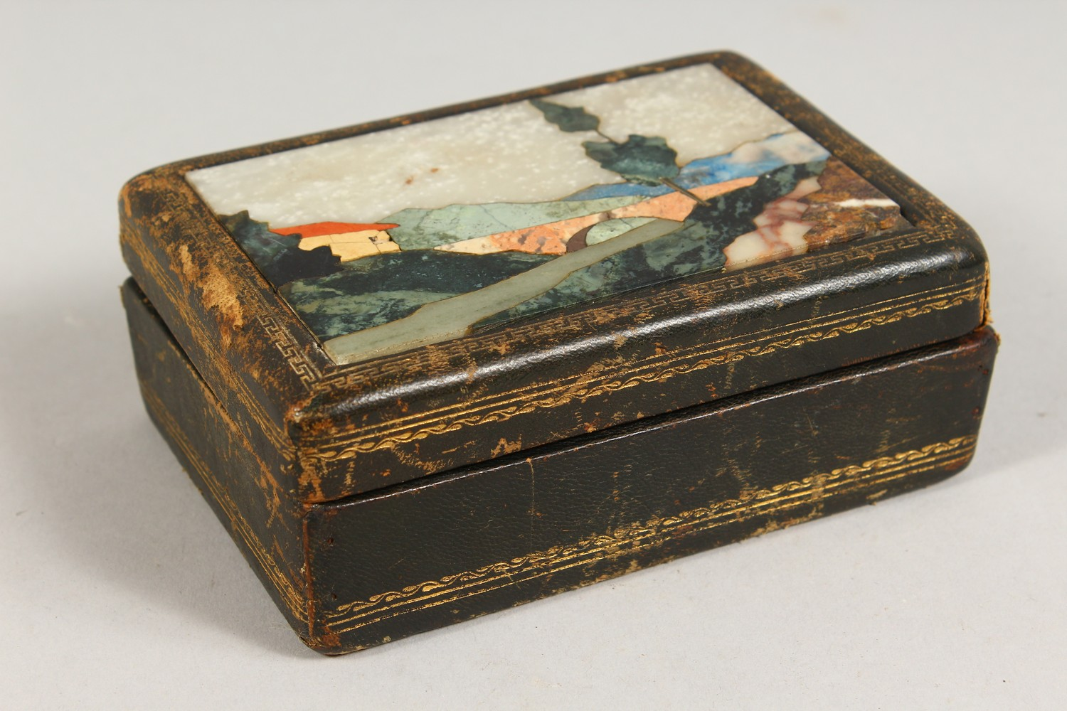 Lot 1429 - A PIETRA DURA AND LEATHER BOX, 20TH CENTURY, the hinged cover inlaid with various hardstones to form