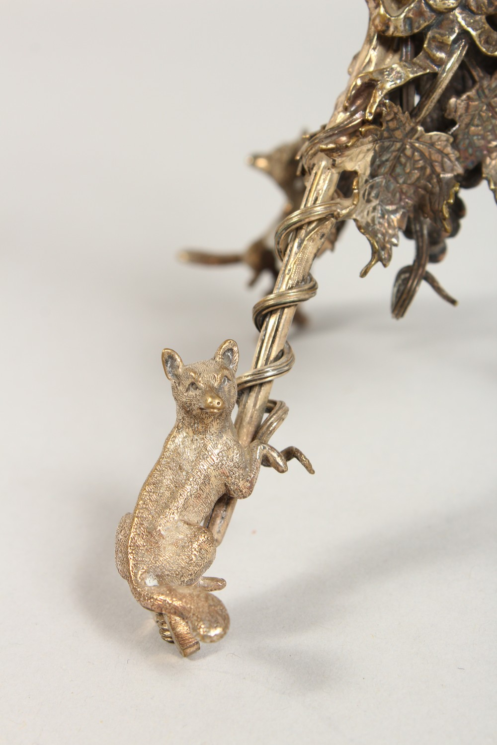 Lot 2052 - A GOOD PAIR OF CAST, PLATED STANDS, modelled as foxes climbing up grapevines. 5.5ins high.