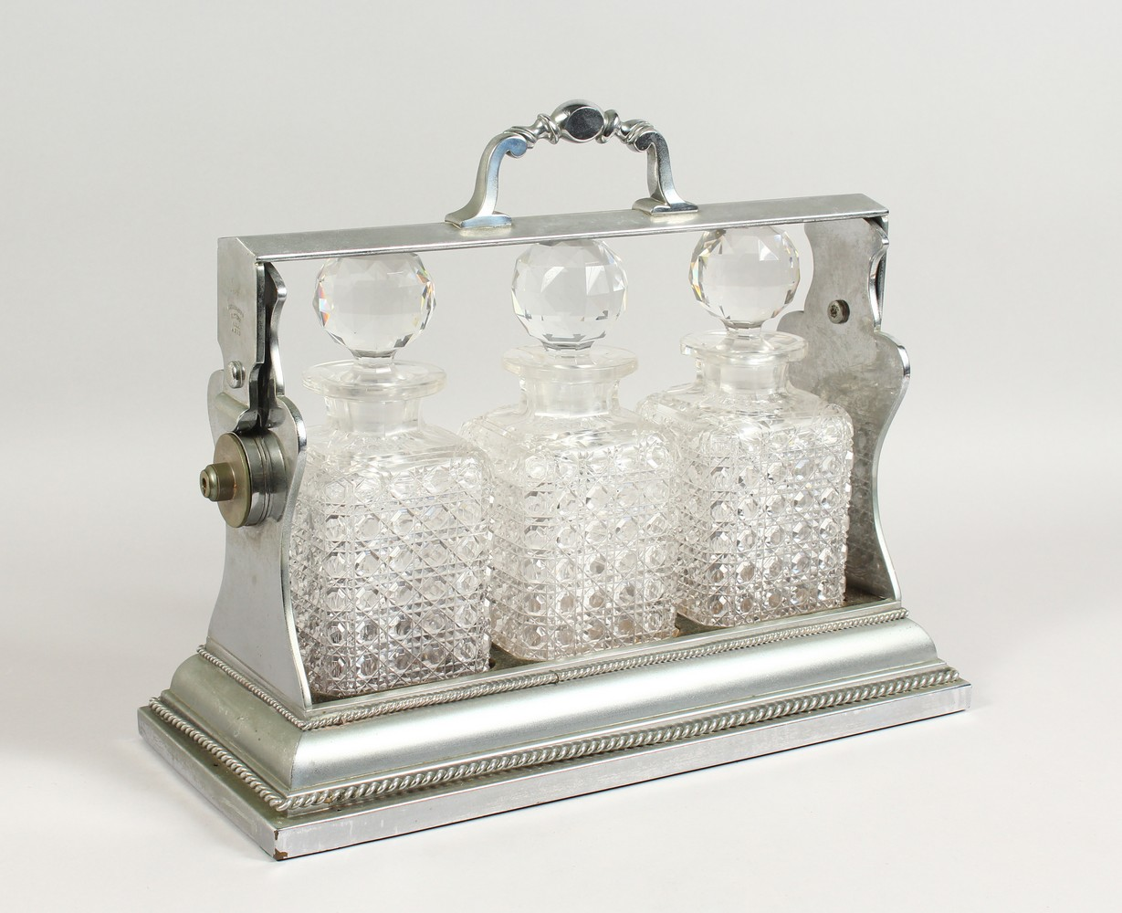 Lot 1570 - A LARGE TANTALUS, with three cut glass whisky decanters and stoppers. Marked Betjemann 4213.