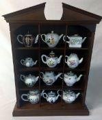Display stand containing 12 Franklin Mint Victoria & Albert replica 18th century tea pots