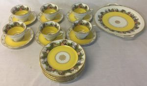 Yellow ground & figural half tea service comprising cups, saucers,