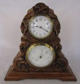 19th century walnut barometer and clock set carved with leaves and scrolls on a stepped plinth H