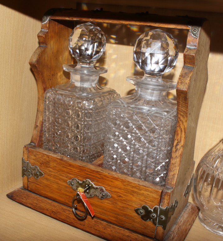 Lot 47 - An oak and metal mounted Tantalus, fitted two cut glass decanters and stoppers, together with two