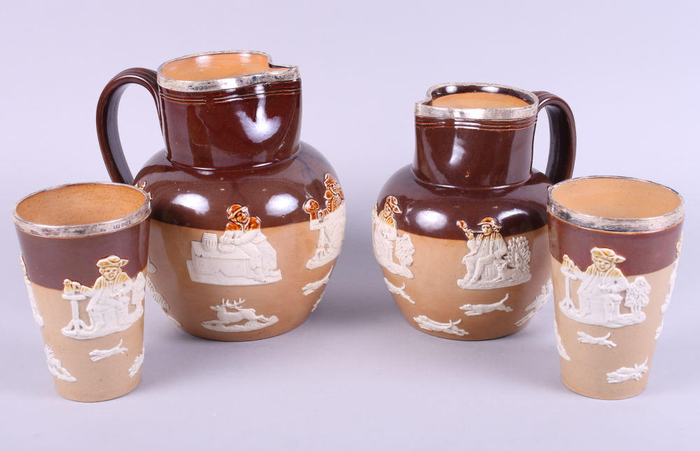 """Lot 3 - A pair of Royal Doulton stoneware silver rimmed beakers, 4 3/4"""" high, and two similar jugs (one"""