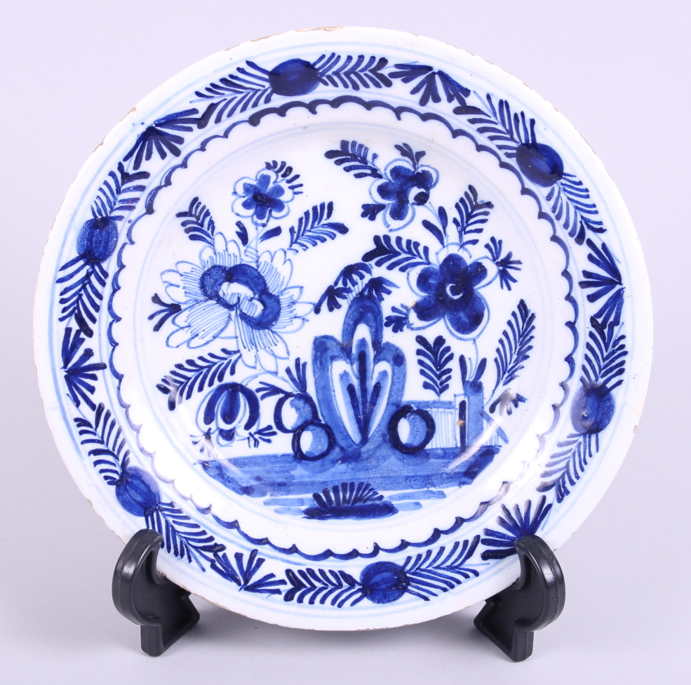 "Lot 1 - An 18th century English delft dish, decorated with flowers and fence, 9"" dia"
