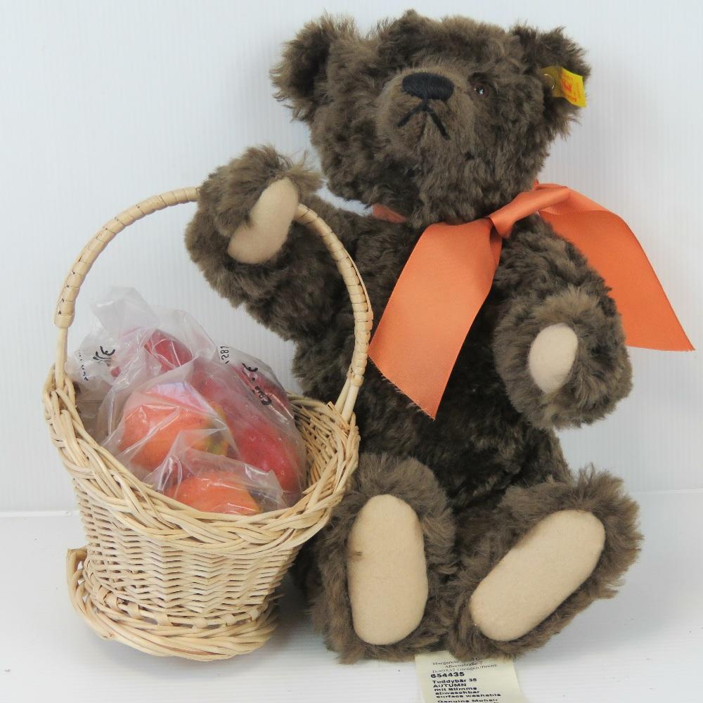 Lot 447 - A Steiff 'Autumn' Teddy bear in brown mohair with a basket of apples, 34cm high.