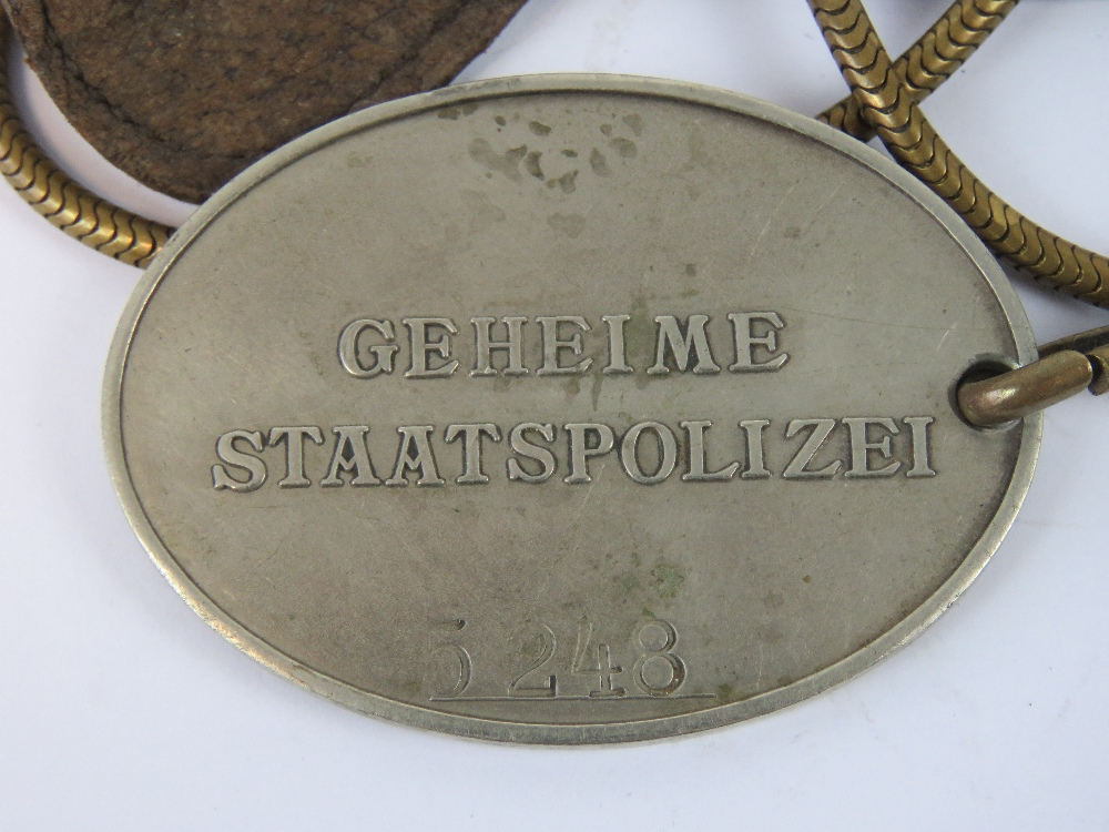 Lot 55 - A Gestapo Officers identification disc with chain hanger and leather fob,