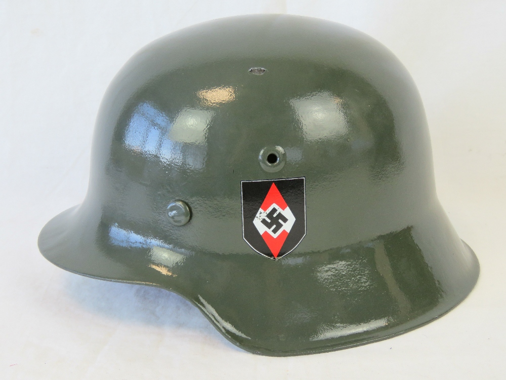 Lot 40 - A reproduction WWII German helmet having leather liner.