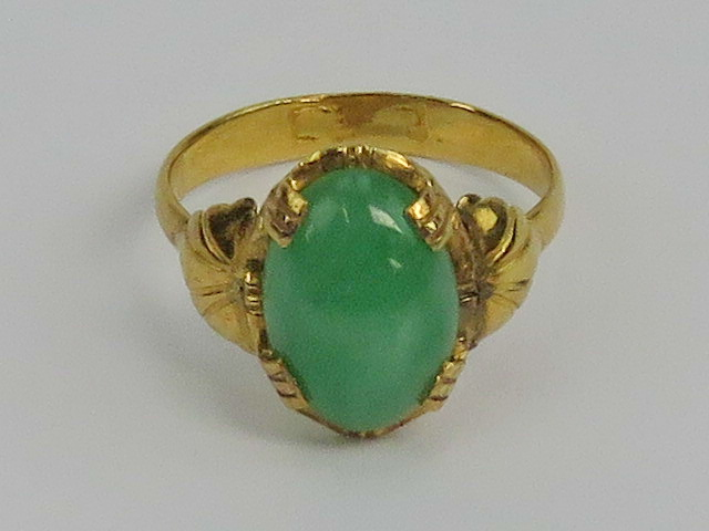 Lot 174 - A green jade and yellow metal ring, the