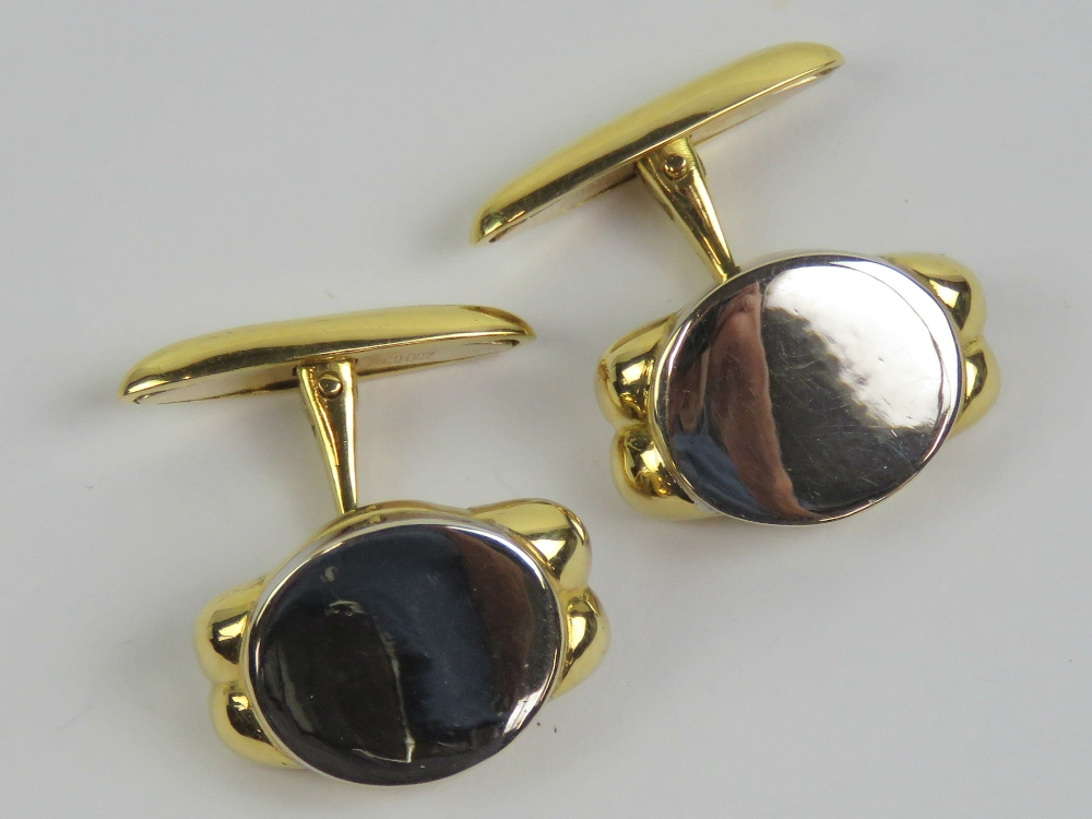 Lot 105 - A pair of 18ct white and yellow gold cufflinks having oval front panel in white gold, unengraved,