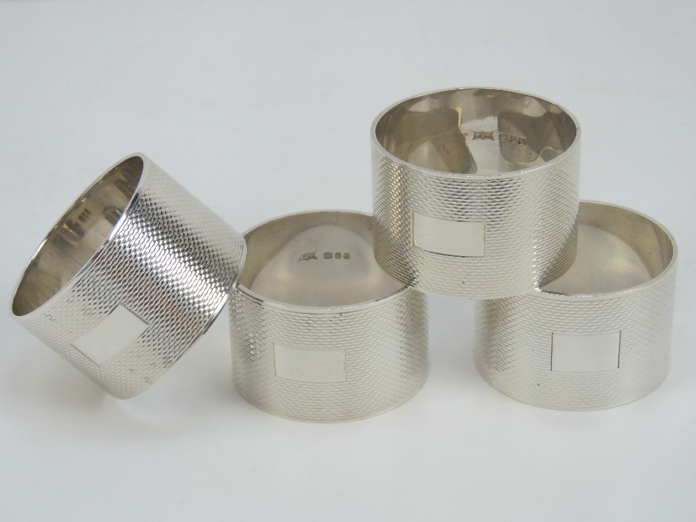Lot 7 - A set of four HM silver napkin rings having engine turned pattern upon with blank cartouche,