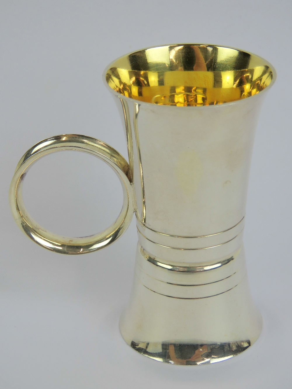 Lot 20 - A HM silver double ended spirit measure having loop handle and gilded interior,