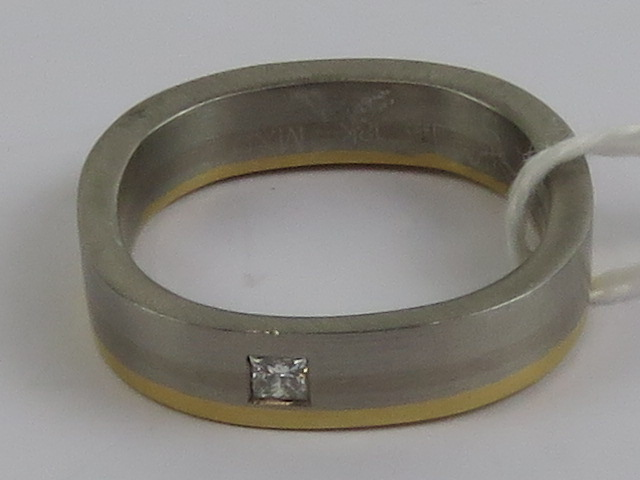 Lot 107 - An 18ct gold and Palladium square shaped ring having princess cut diamond to front,