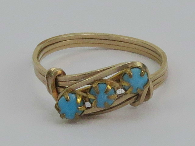 Lot 121 - A yellow metal wirework ring set with three turquoise cabachons, size P, 1.6g.