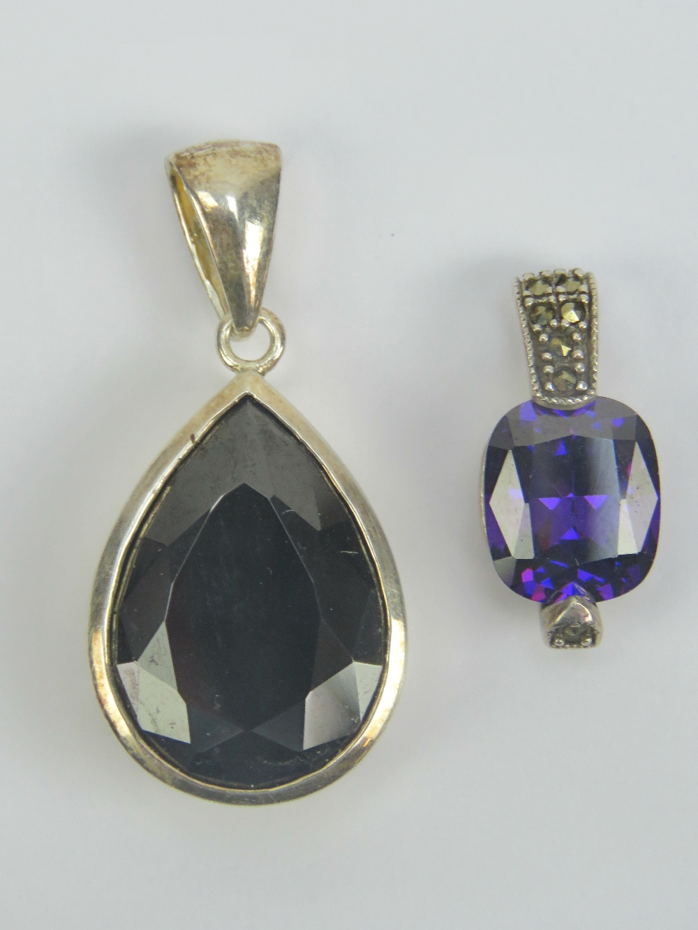 Lot 102 - A silver pendant having large central faceted amethyst and bale set with marcasites, stamped 925, 2.