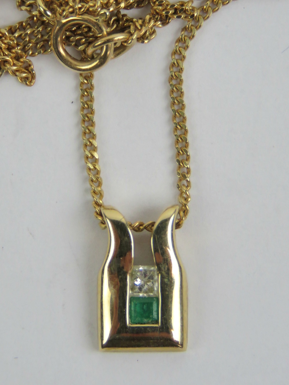 Lot 103 - A 9ct gold diamond and emerald pendant, the square cut emerald and diamond in channel setting,