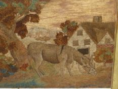 AN EARLY 19th.C. WOOLWORK PICTURE OF A DONKEY GRAZING BY A TREE OUTSIDE A COTTAGE
