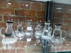 SIX SILVER MOUNTED WHISKEY TOTS, B'HAM 1910-11, FIVE WITH BOTTLE LABELS, EACH OF CONICAL SHAPE
